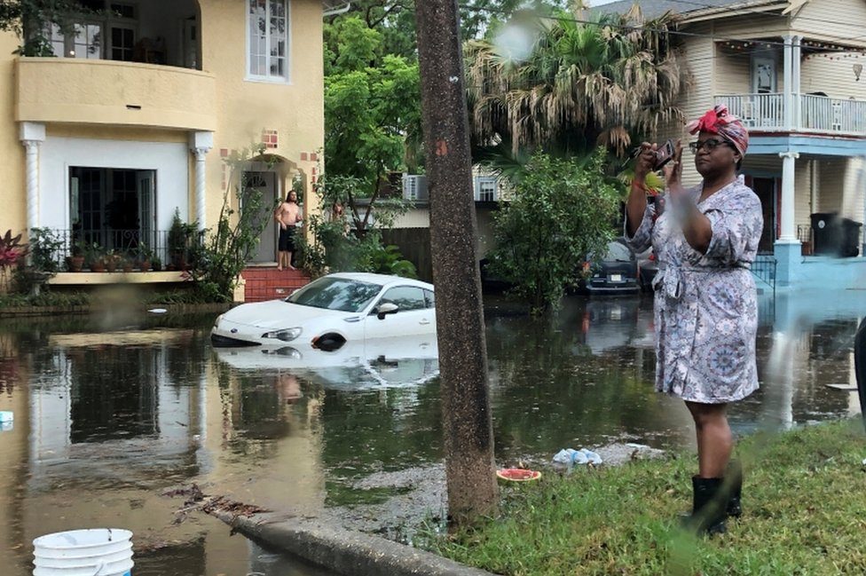 Una mujer toma una foto en una calle inundada de Luisiana.