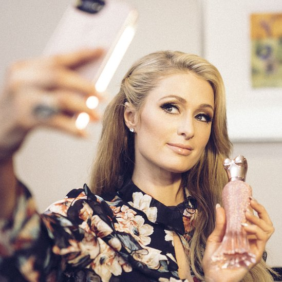 Photograph shows Paris Hilton taking a photograph with her fragrance bottle