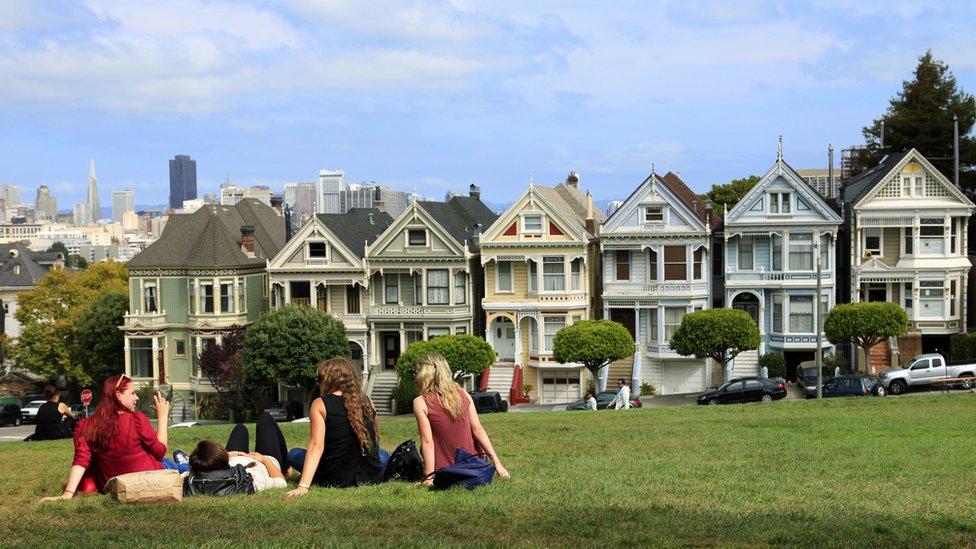 Grupo de mujeres sentadas frente a un complejo de casas.