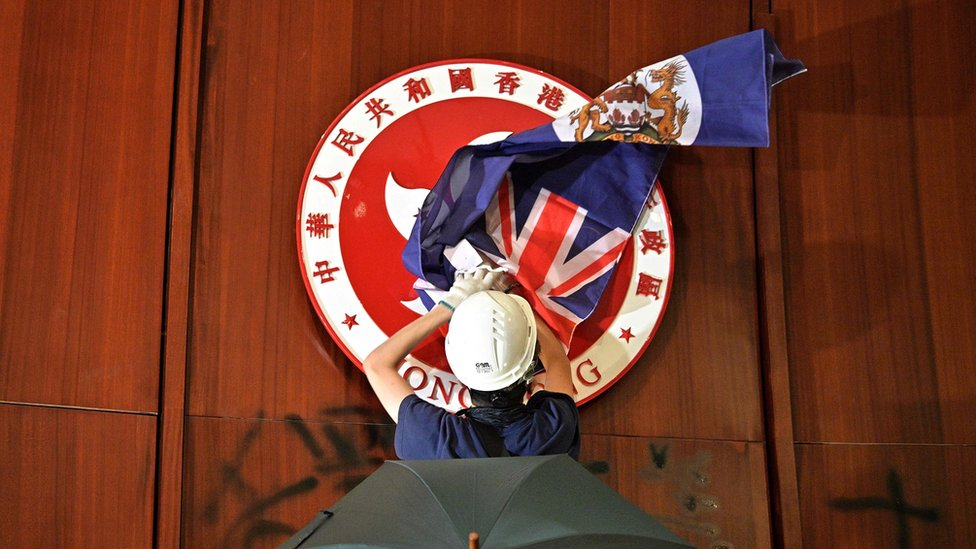 Protester covering the Hong Kong emblem with a British colonial flag