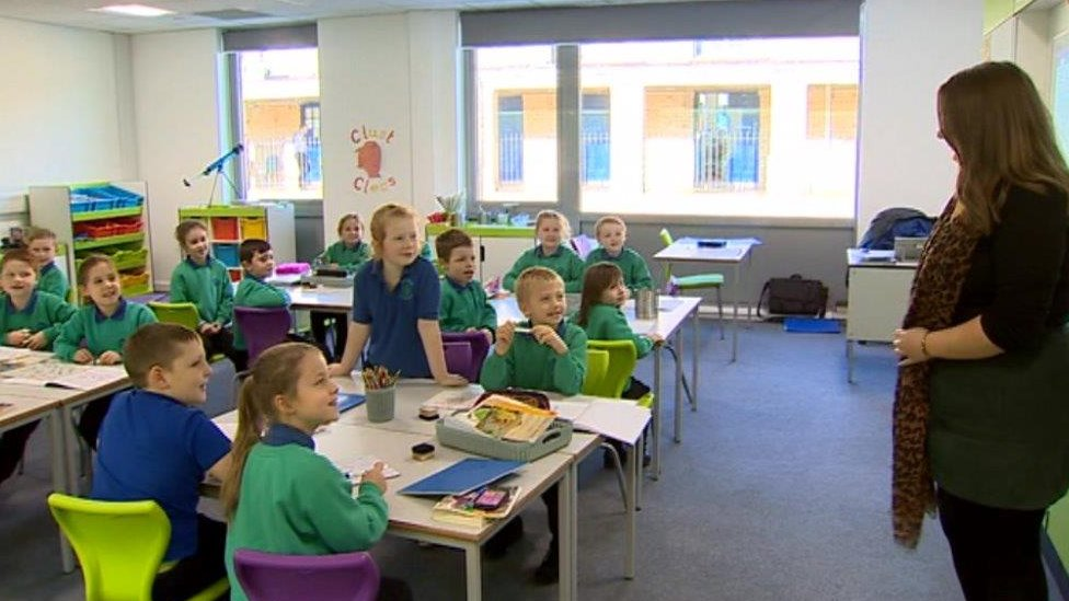 Children in class smile at their supply teacher