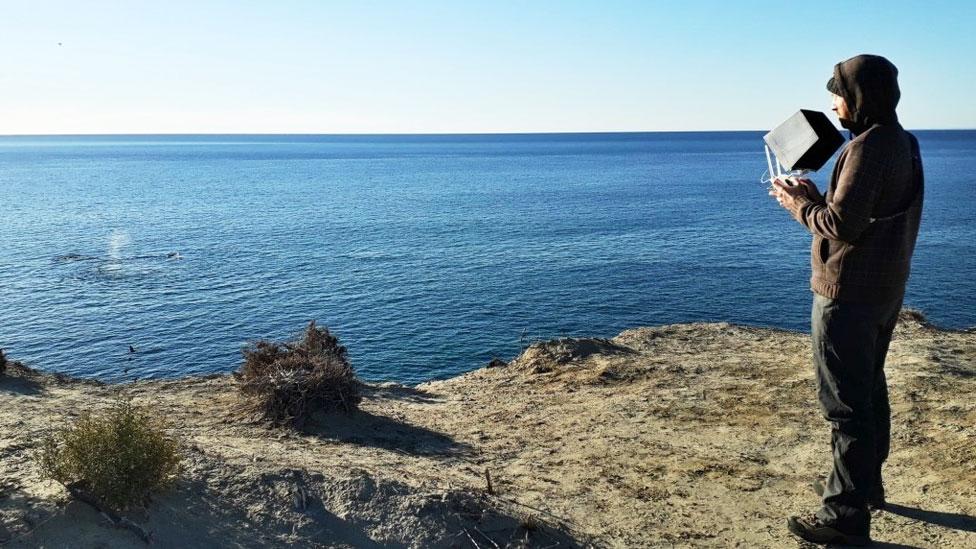 Fredrik Christiansen frente al mar operando un dron