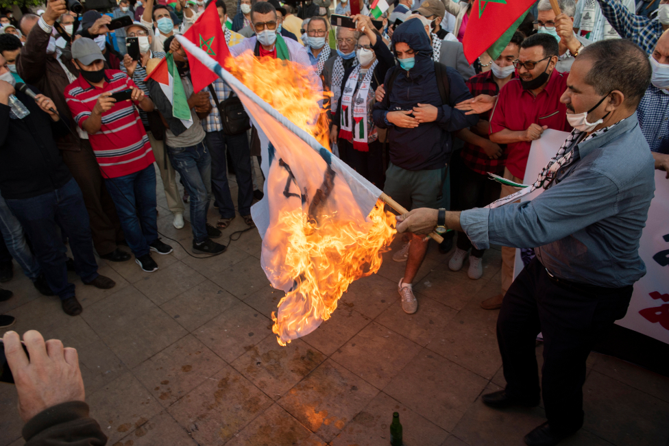 People burn an Israeli flag during a protest against the normalization of relations with Israel and symbolic stand of solidarity with Palestinians, in front of the Parliament headquarters in Rabat, Morocco, 18 September