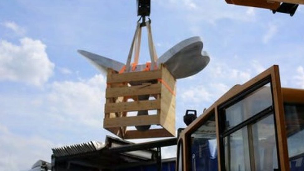 The sculpture is loaded in crates