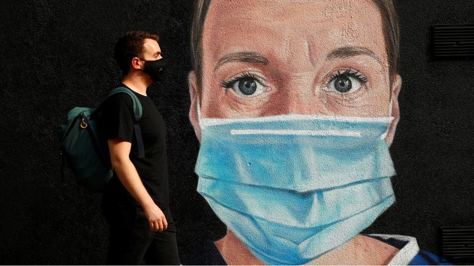 A man wearing a protective face mask walks by a mural of a medical worker in Manchester city centre