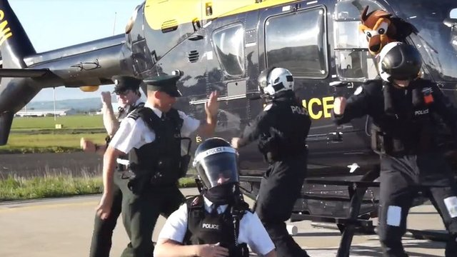 Police officers doing the running man dance