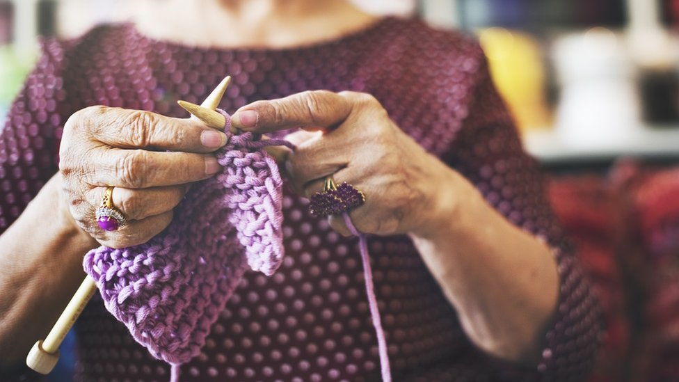 Woman with beautiful purple rings, knitting some purple yarn. She's wearing a purple top
