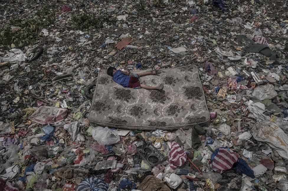 A boy lies on a mattress amongst rubbish