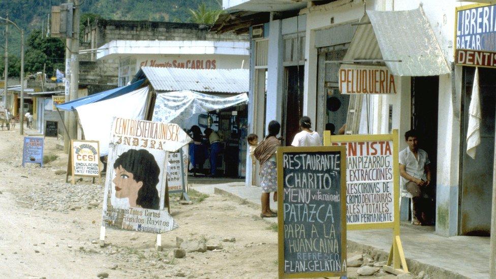 Carteles de tiendas y una calle en Pichanaki