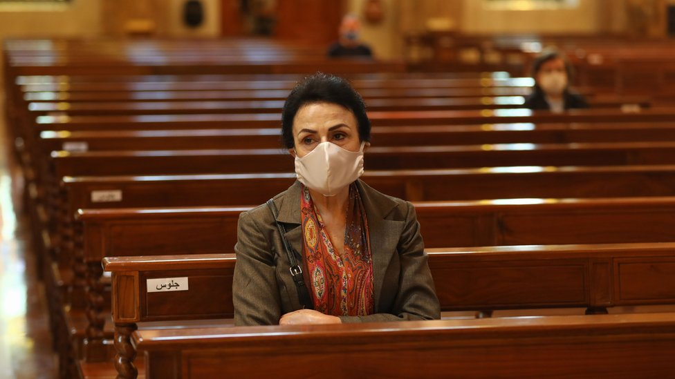 A woman sits in a church in Lebanon