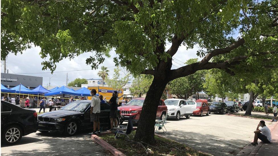 Autos en fila esperan que empiece la distribución gratuita de alimentos