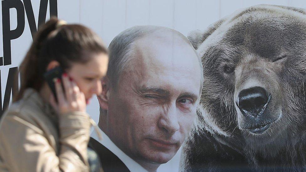 Una mujer con un celular frente a un retrato de Vladimir Putin