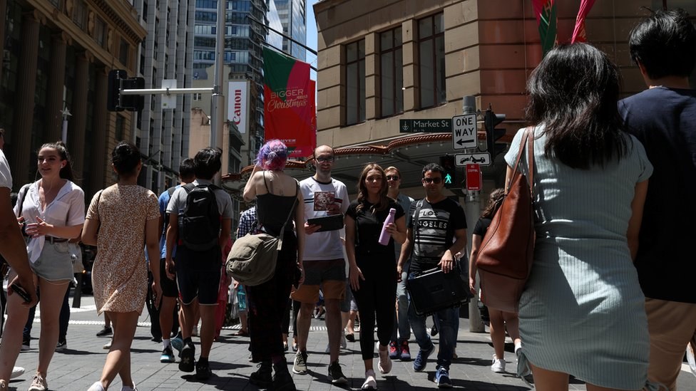 A crowd crosses a busy road in Sydney's central shopping district