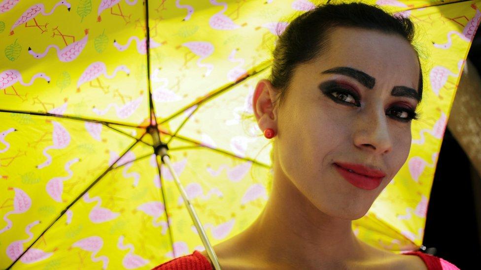 Mujer trans con una sombrilla amarilla