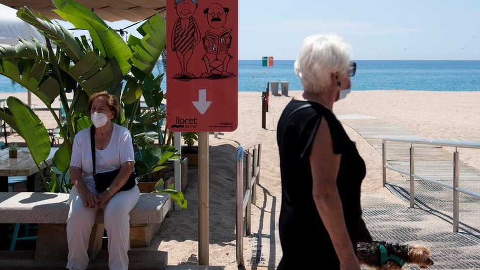 A woman walks her dog past another woman sitting on a Spanish beach