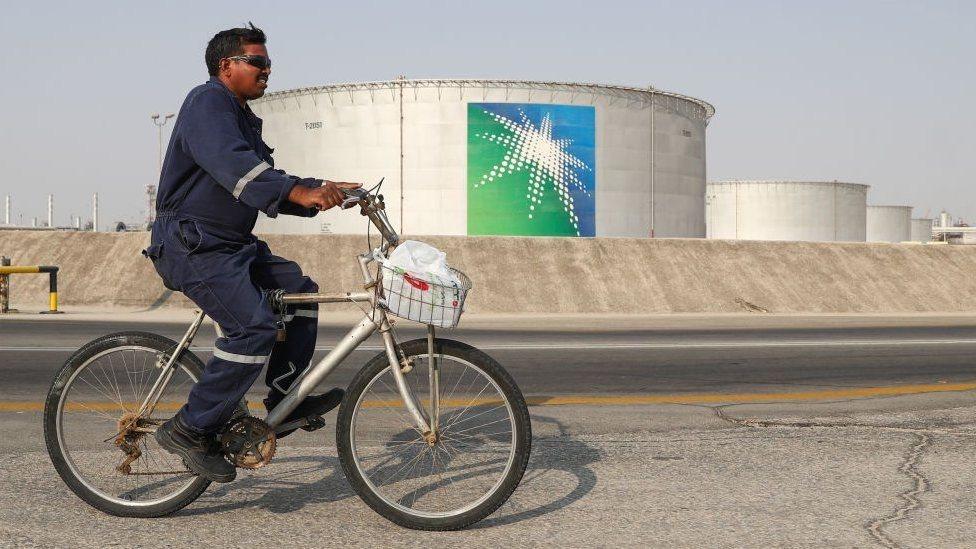 شخص يستقل دراجة مارًا من أمام شركة نفطية
