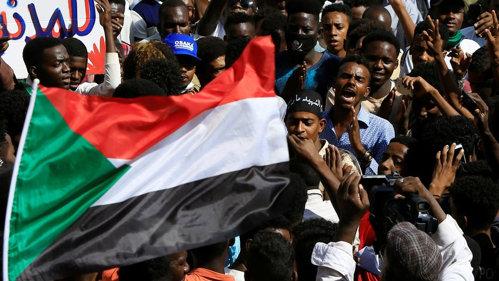 People at rally in Khartoum with Sudanese flag
