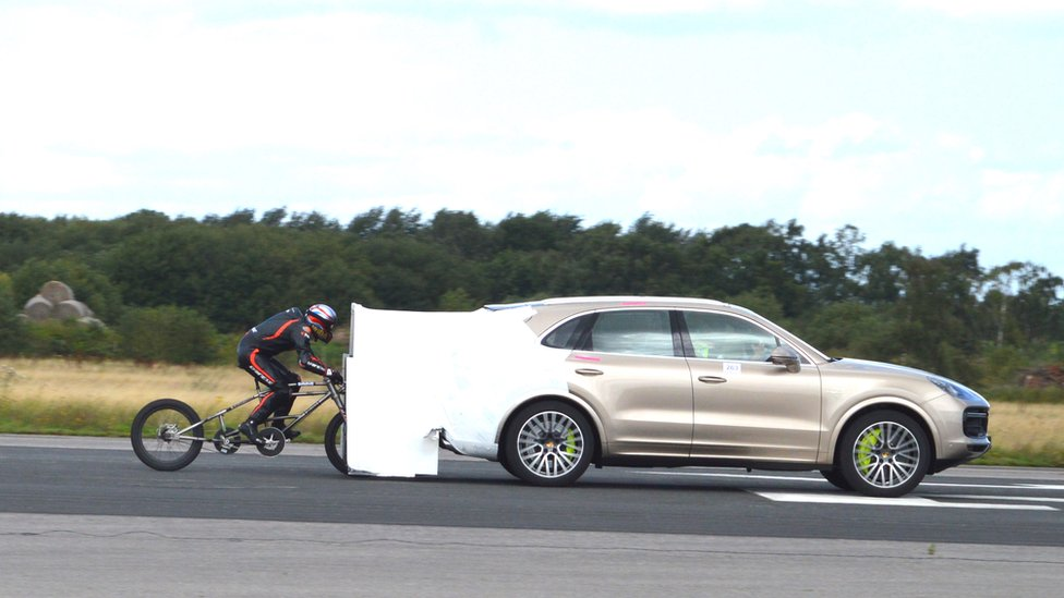 Neil Campbell being pulled along on a bike behind a Porsche Cayenne before he was released