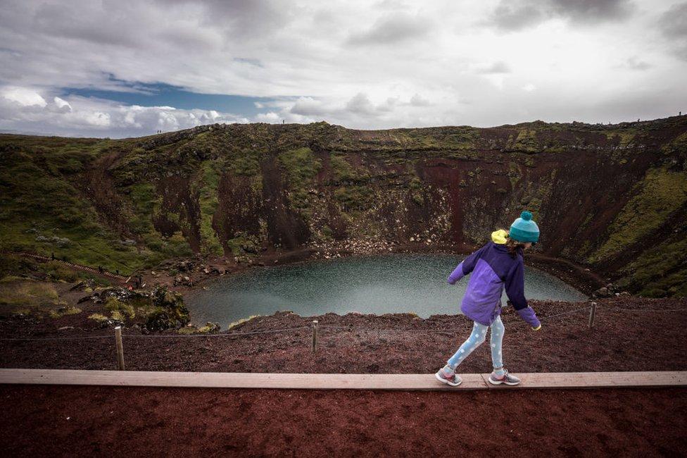 Niña camina frente a un cráter en Islandia.