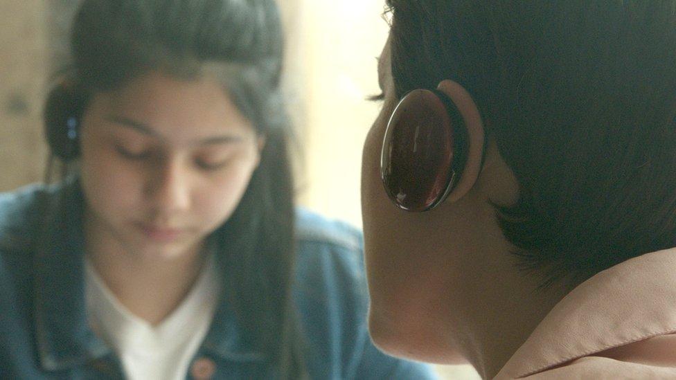 Dos personas con auriculares de traducción de la empresa Waverly Labs