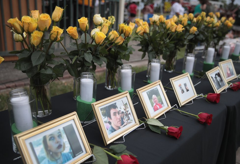 Pictures of Santa Fe school shooting victims stand by white candles and yellow roses