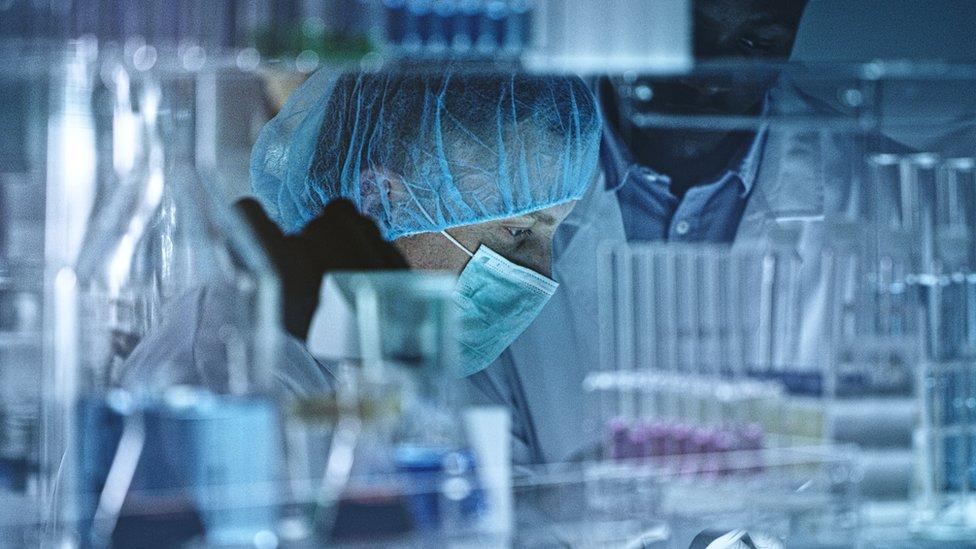 Dois cientistas em laboratório, em meio a vários tubos e equipamentos
