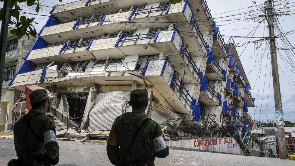 Soldados vigilan un edificio derrumbado