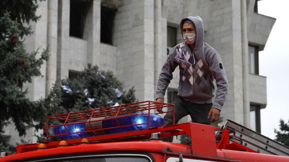 Protester stands on a fire engine in Bishkek on 6 October 2020