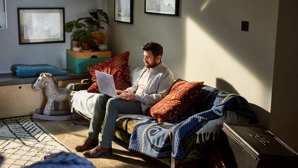 Hombre sentado con una laptop en un sofá