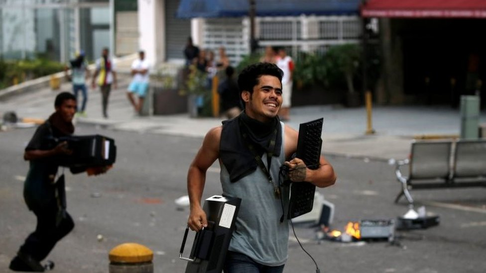 People run with looted items in Caracas. Photo: 19 April 2017