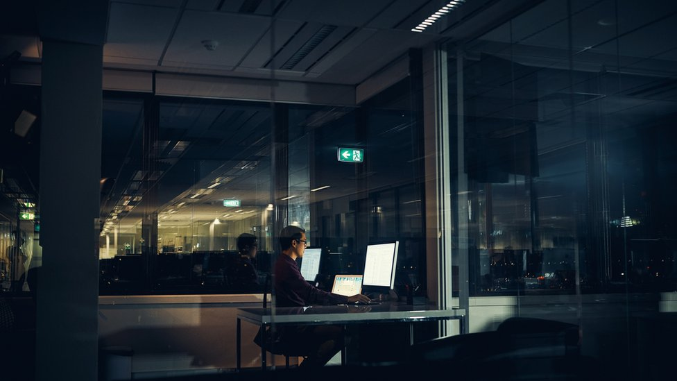 Man works alone in office at night