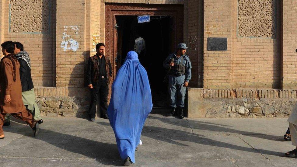 Una mujer entra en un edificio en Herat