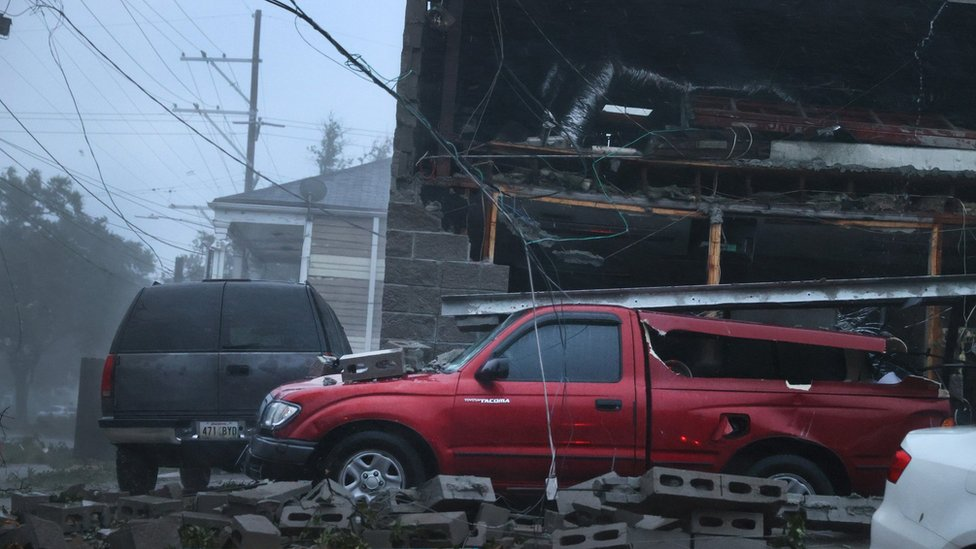 Vehicles damaged by collapsed building in New Orleans as Hurricane Ida makes landfall.