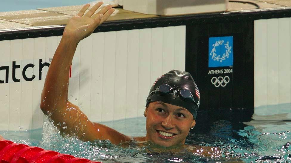 Tara Kirk Sell saludando en un extremo de una piscina