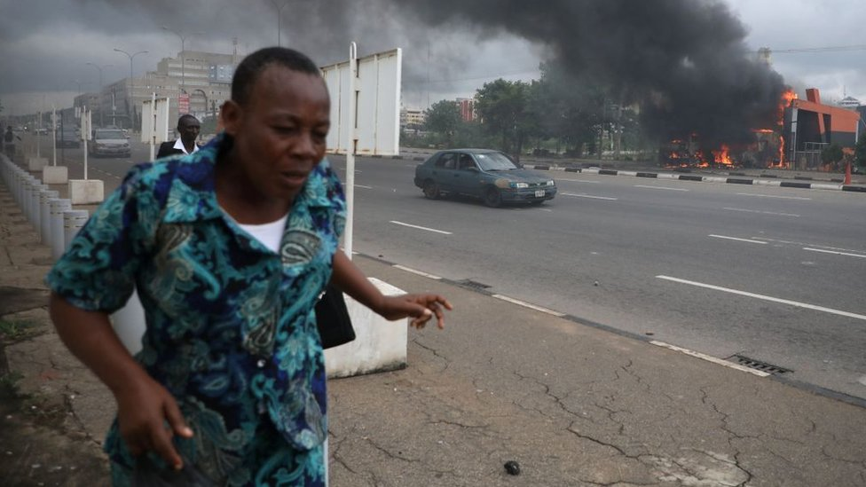 People walk past a fire service station set ablaze by members of the Shia Islamic Movement in Nigeria (IMN) during clashes with the police in the streets of Abuja on July 22, 2019.