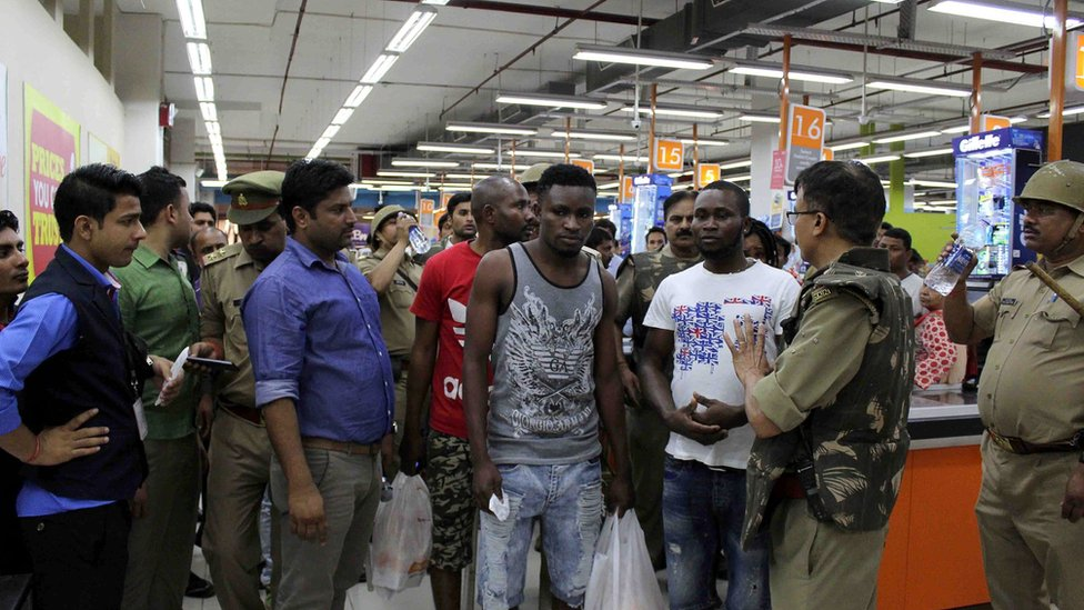 This photo taken on 27 March 2017 shows Indian police and onlookers surrounding African nationals at a shopping mall in Greater Noida