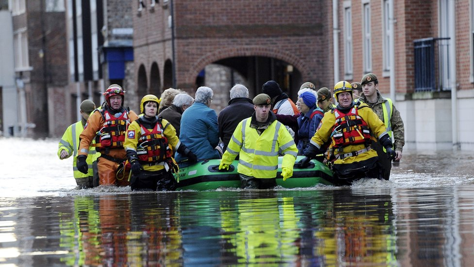 Members of the army and rescue teams help evacuate people from flooded properties after they became trapped by rising floodwater when the River Ouse bursts its banks in York city centre in December 2015