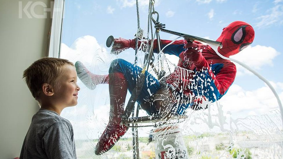 A child smiles as 'Spiderman' scrubs the window from the other side