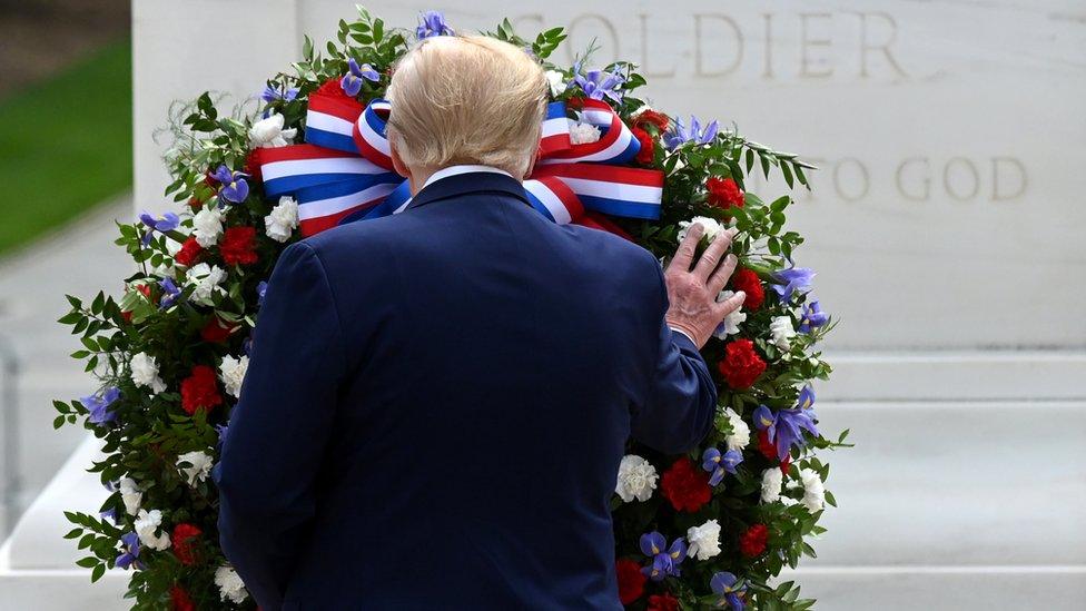 الرئيس الأمريكي دونالد ترامب يمد يده ويلمس إكليلاً من الزهور خلال المراسم التذكارية أمام قبر الجندي المجهول في مناسبة يوم الذكرى، 25 مايو/أيار 2020