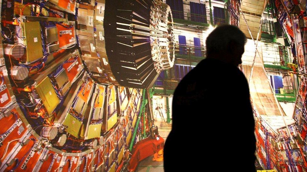 Un trabajador pasa frente a una fotografía gigante del Gran Colisionador de Hadrones.