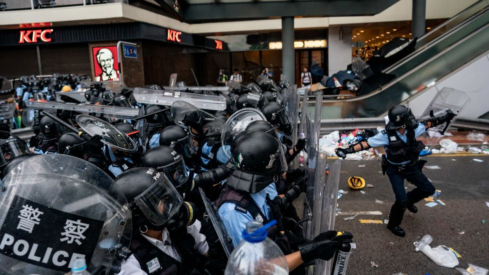 A police officer throws a teargas canister during a protest on June 12, 2019 in Hong Kong China