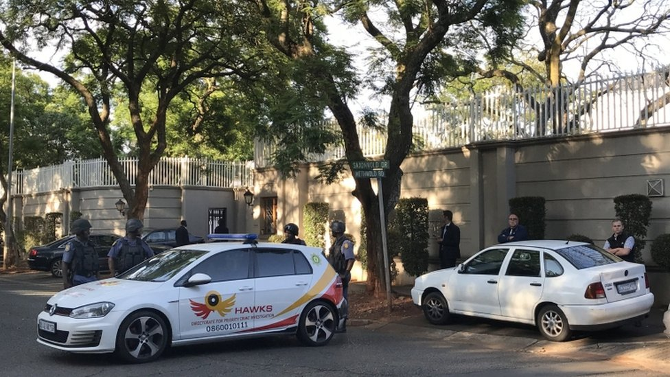 Members of the Hawks special police unit stand guard outside Gupta home