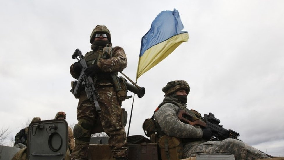 Ukrainian servicemen ride on an armoured personnel carrier (APC) at a checkpoint near the eastern Ukrainian town of Debaltseve in Donetsk region (24 December 2014)