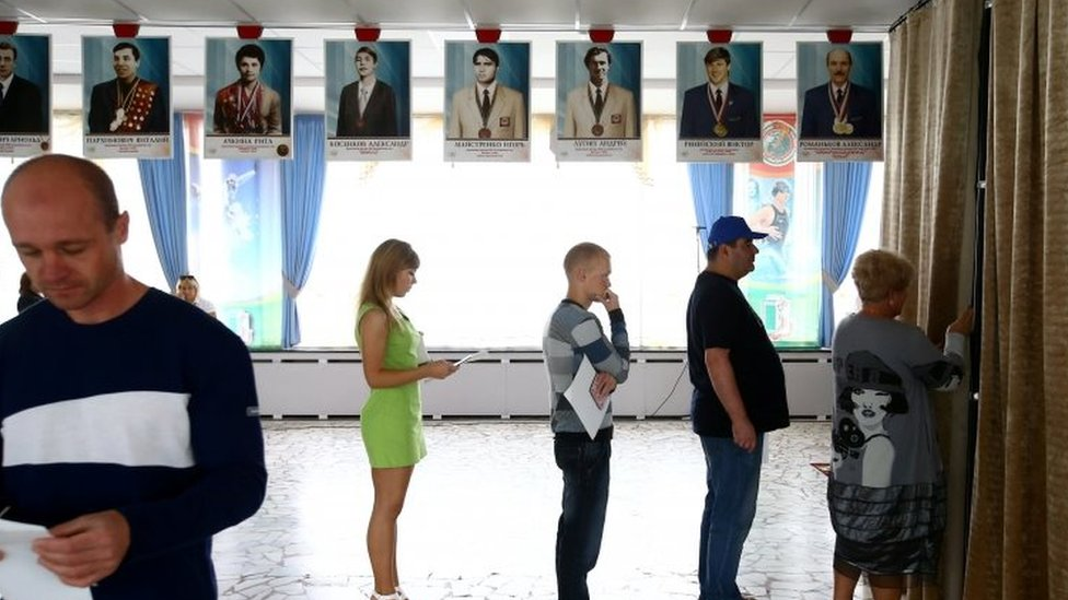 People wait in a queue in front of a voting booth during a parliamentary election at a polling station in Minsk (11 September 2016)