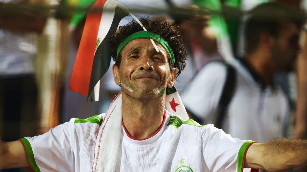مشجع جزائري يرفع العلم المصري على رأسه خلال مباراة نصف النهائي أمام نيجيريا