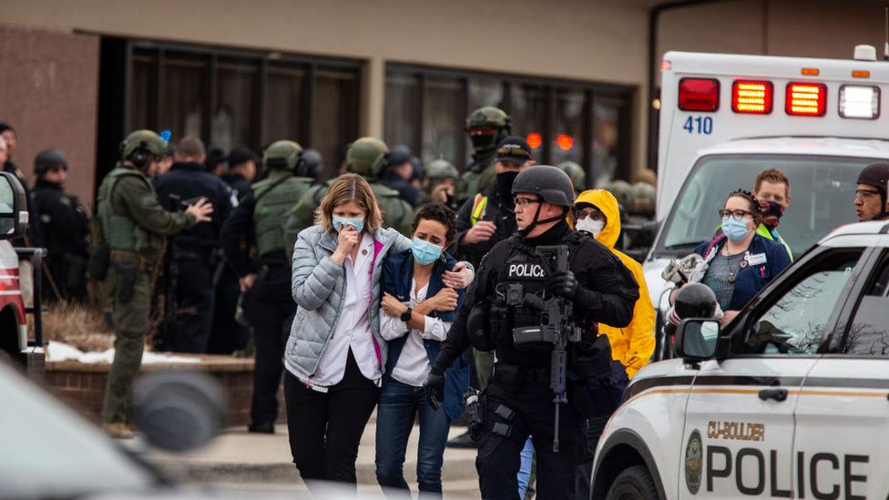 Healthcare workers walk out of a King Sooper's Grocery store after a gunman opened fire on 22 March 2021 in Boulder, Colorado