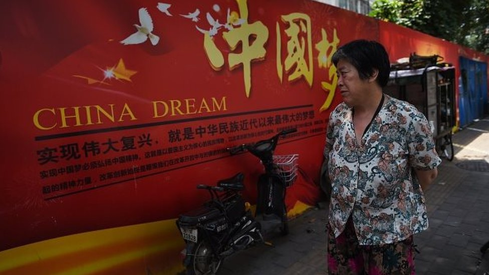 A woman looks at a banner about the 'China Dream', Chinese President Xi Jinping's vision for China's future, in Beijing on July 7, 2015