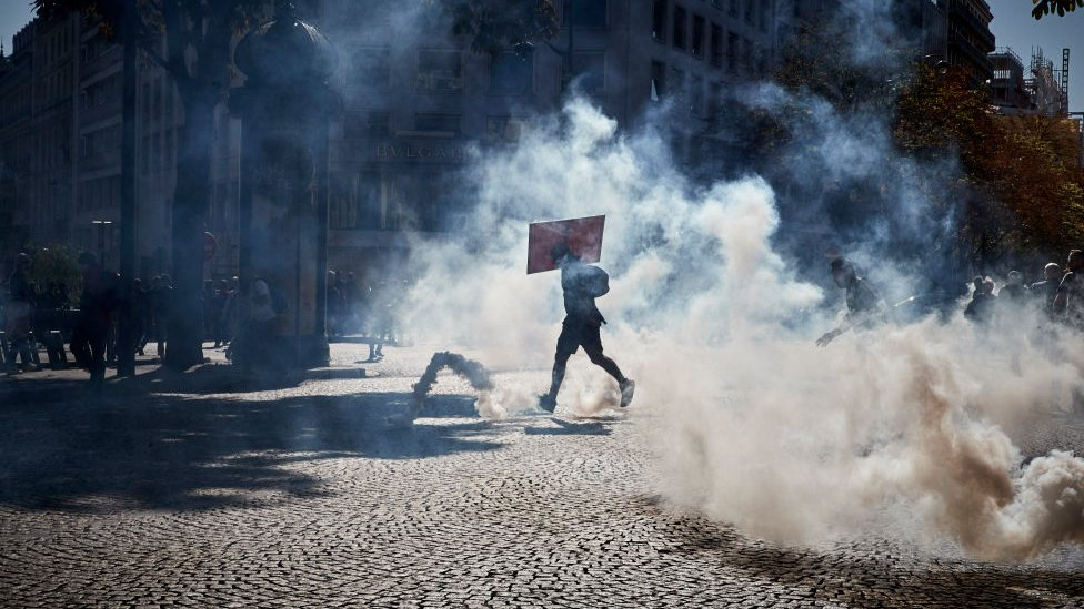 Activists run through clouds of tear gas