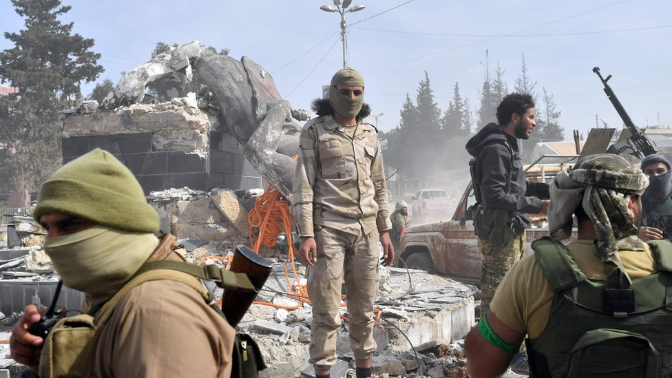 Turkish-backed Syrian rebels gather next to the destroyed Kawa statue in the city of Afrin in northern Syria on March 18, 2018