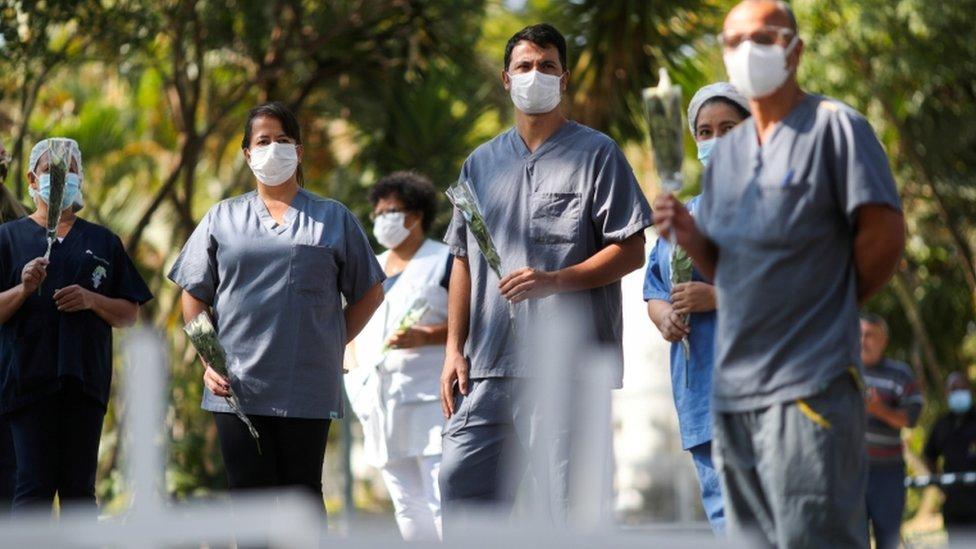 Médicos con rosas en la mano para homenajear a una enfermera que murió por coronavirus.